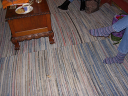 Picture of the floor which has an old rag rug which is sewn together in sections and has a hole in it.