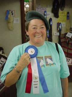Woman showing fair ribbon and wearing the felted hat