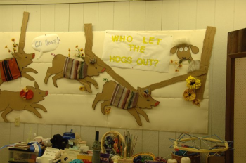 Display board with hogs and theme of fair, who let the hogs out