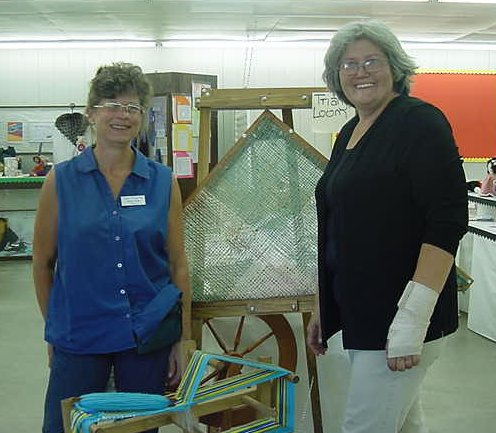Fair managers posing in front of triangle loom