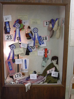 Display case full of items with fair ribbons