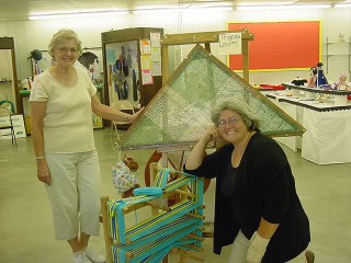 Two women posing in front of triangle loom