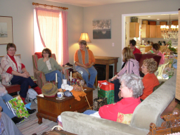 People sitting around smiling with presents sitting on floor and tables.