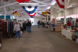 Inside barn, vendors on both sides, colorful banners on rafters.
